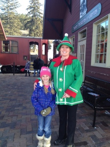 Jessica poses with an 1880 Train elf in front of the Holiday Express.
